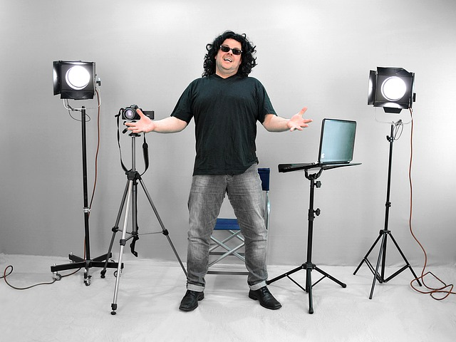A guy standing in the middle of a video camera and video lights.